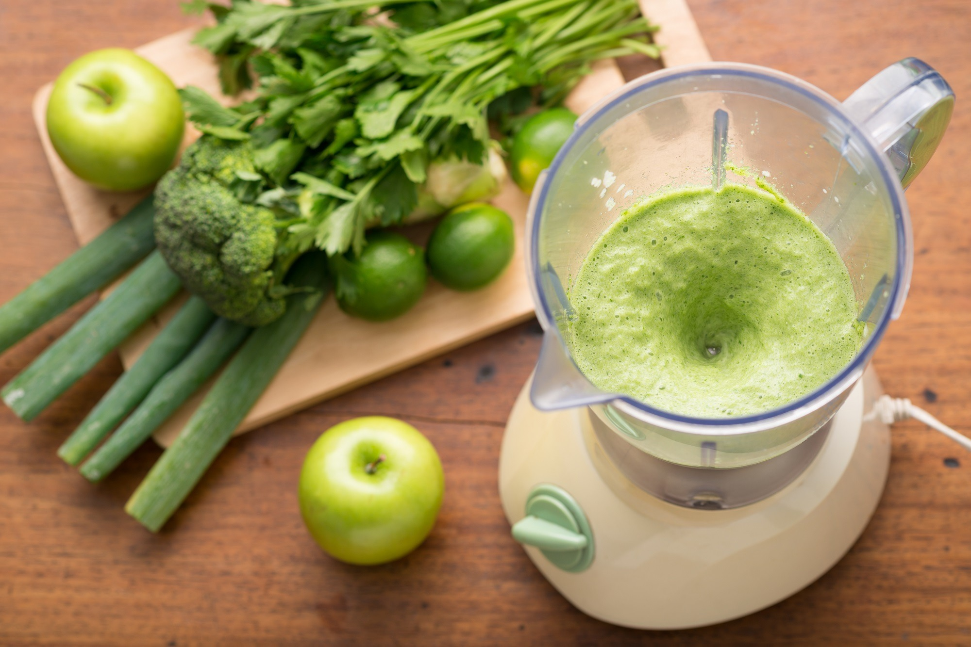 Blender with green fruits and vegetables