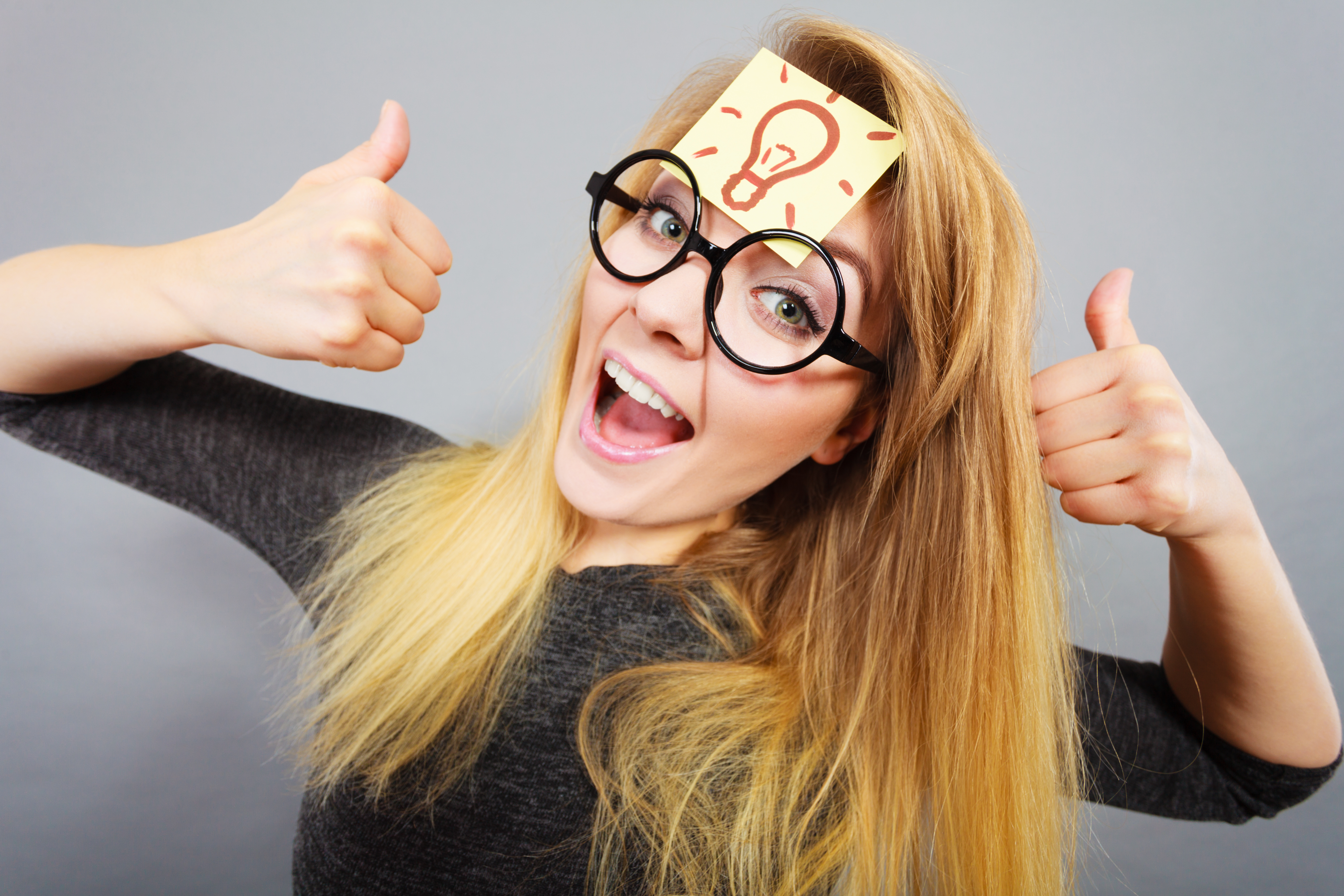 Woman with Post It note on forehead, giving thumbs up