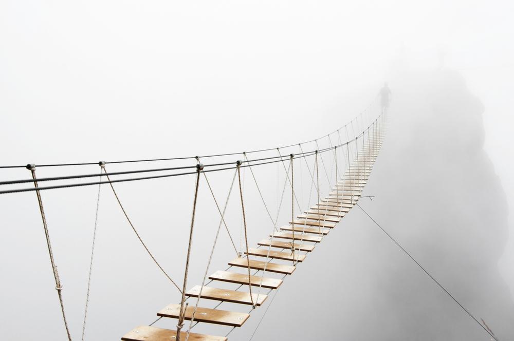 Fuzzy man walking on hanging bridge vanishing in fog