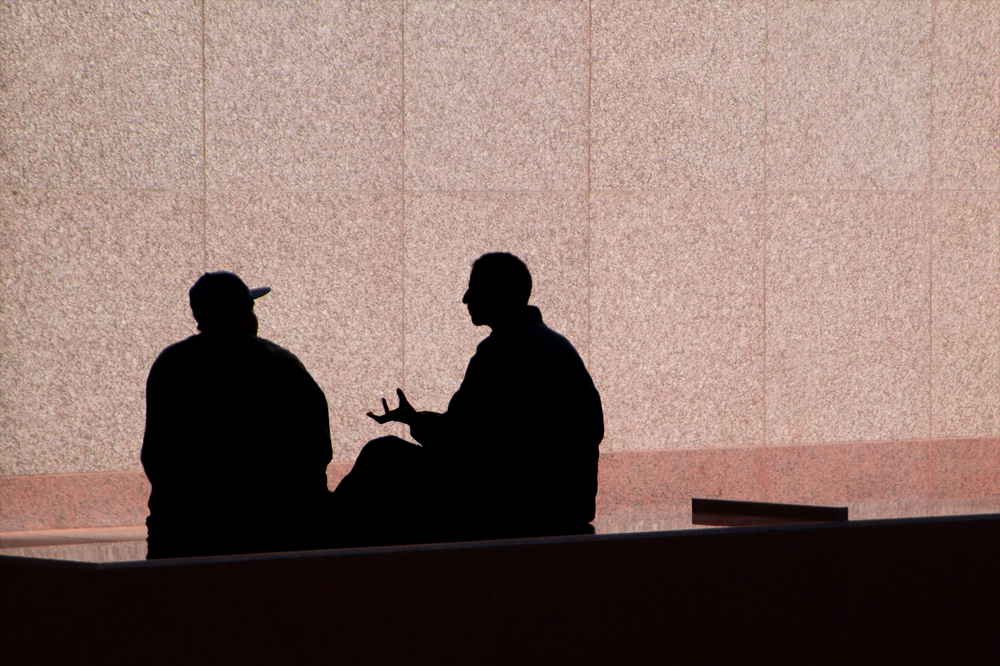 Two men talking and they are silhouetted